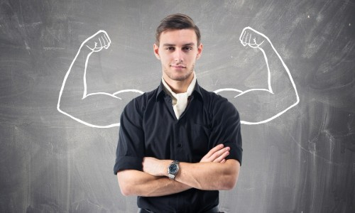 Man standing in front of chalkboard with strong muscles flexing drawn in behind him